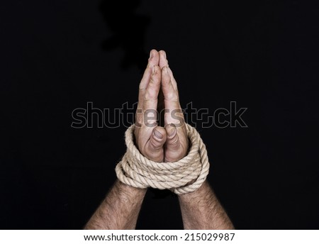 Men's hands tied a rope isolated on a black background - stock photo