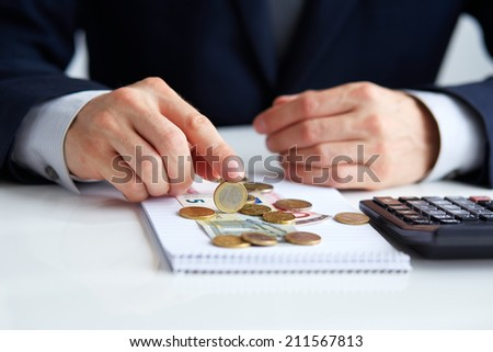 Men's hands with coins euros. Calculation at office  - stock photo