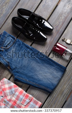Men's jeans, shirt and accessories on a wooden background. - stock photo