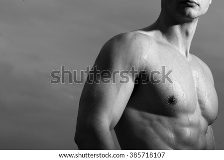 Men's nude chest with inflated muscles with drops of sweat on sky background, black and white, horizontal photo - stock photo