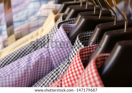 Men's plaid shirts in different colors on hangers in a retail shop - stock photo