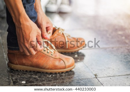 Men's shoes tying shoelaces. - stock photo