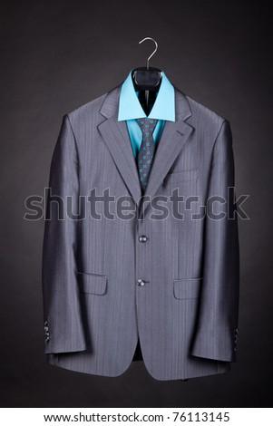 Men's suit on the rack, elegant men suit over gray background concept. - stock photo