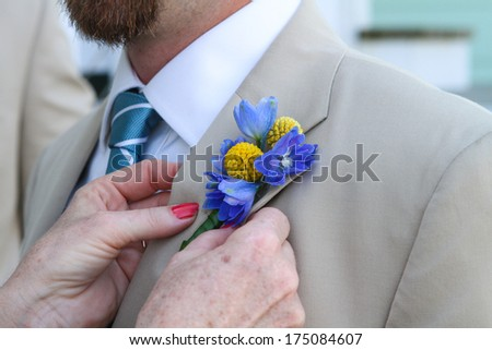Men's suit up close, pinning flowers - stock photo