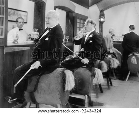 Men sitting at a bar on horse back - stock photo