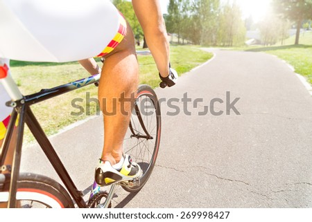 Men sport riding a bicycle in the park at asphalt road - Close up of bike wheel and cyclist foot on pedal - Guy in technical clothing city bike - Active concept outdoors - Focus on the hand - stock photo