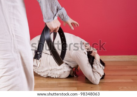 Men threadting and beating his wife at home with a belt - stock photo