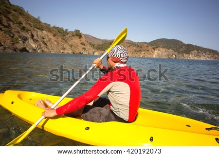 Men travel by canoe on the sea in the summer.  - stock photo