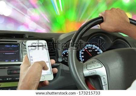Men use the telephone to send text messages to friends while driving at speeds of 70 miles per hour on the dial. Danger of accidents and is illegal by the government  - stock photo