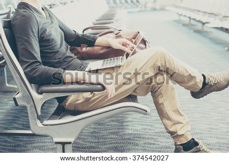 Men using a laptop in the waiting room of the airport - stock photo