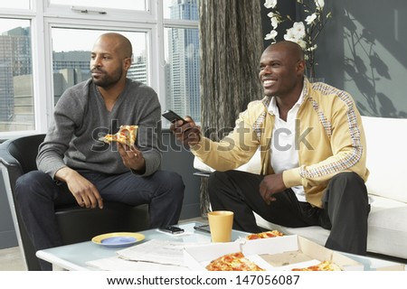 Men watching television and eating pizza in living room - stock photo