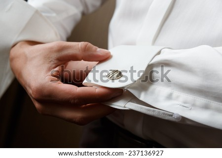 men wear cufflinks on a shirt sleeve - stock photo