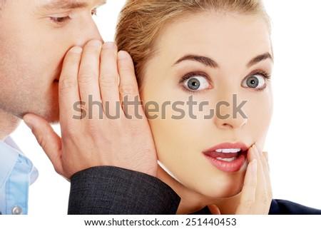 Men whispering secret to his surprised friend - stock photo