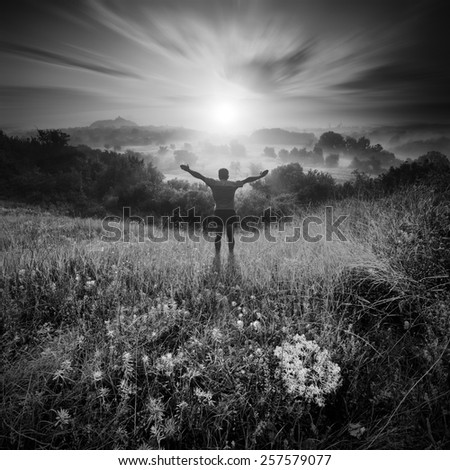 Men, who welcome sunrise with raised hands and enjoying landscape. Monochrome colors - stock photo