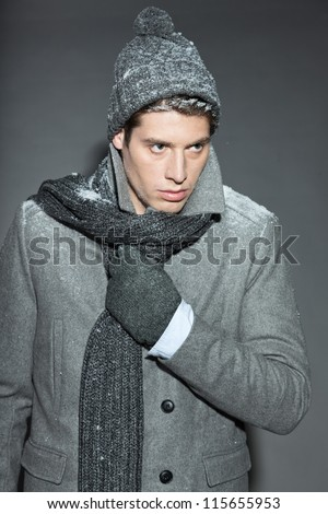 Men winter fashion. Handsome man with brown hair wearing grey scarf, grey woolen hat, grey woolen gloves and grey coat. Covered with snow. Cold. Casual look. Studio shot isolated on grey background. - stock photo