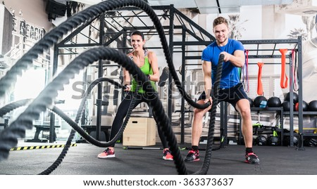 Men with battle rope in functional training fitness gym - stock photo