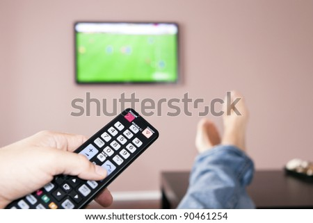 Men with the remote control, front of the television. - stock photo