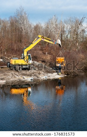 men working with a grab dredger on a lake - stock photo