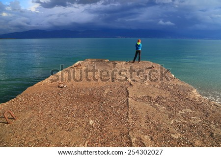 Menacing clouds above stone pier and isolated woman standing by the sea, Greece - stock photo