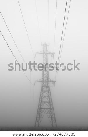 Menacing power line tower in fog - stock photo