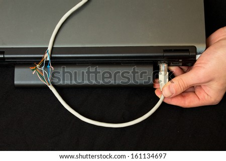 mended twisted pair is inserted into the notebook - stock photo