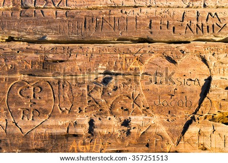 MENDOCINO, CA - Dec 26, 2015: Hearts, initials and names carved into an old  wooden bench in this coastal town about 3 hours north of San Francisco. Popular destination for couples and honeymooners. - stock photo