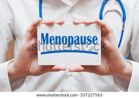 Menopause concept written on a card in doctors hands - stock photo