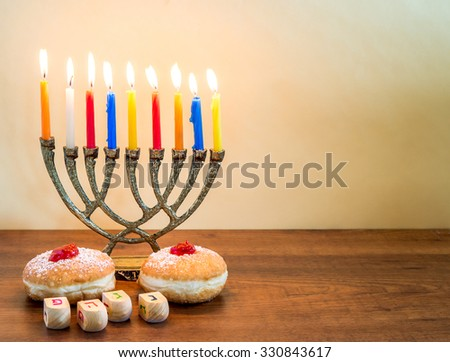 Menorah with candles, donuts with jelly and wood dreidel with Hebrew  caps words for   Hanukkah celebration. - stock photo