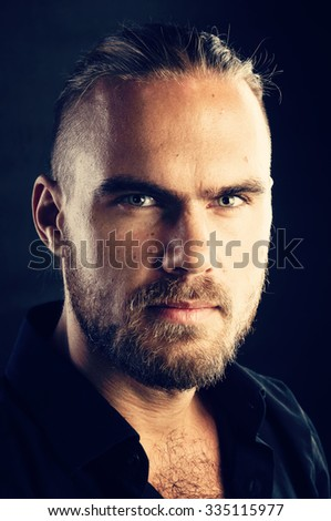 Mens beauty. Portrait of confident young man looking in camera on dark background - stock photo