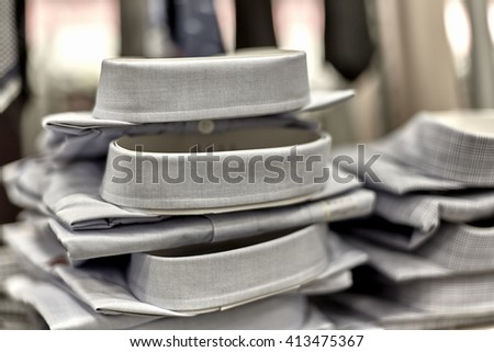 Mens dress shirts stacked on shelf in department store with neckties in the background - stock photo