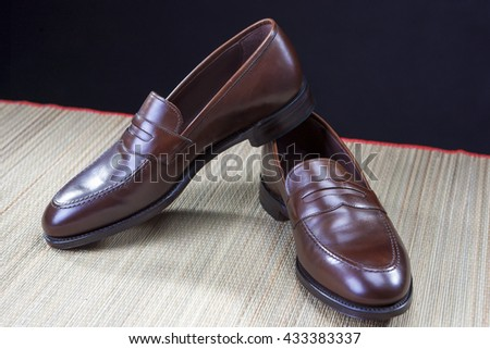 Mens Footwear Concepts. Pair of Stylish Brown Penny Loafer Shoes Placed on Straw Surface against Black.Horizontal Image - stock photo