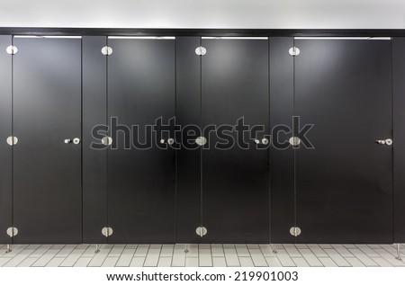 Mens restroom in an public building white black doors - stock photo