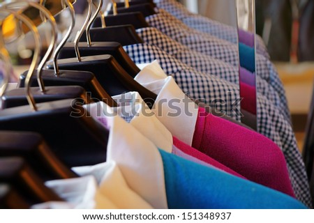 Mens sweaters and shirts in different colors on hangers in a retail clothes store - stock photo