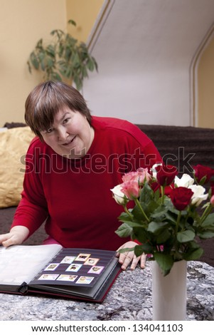 Mentally disabled woman looks at her collection of Stamps - stock photo