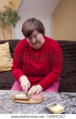 mentally disabled woman makes herself a sandwich - stock photo