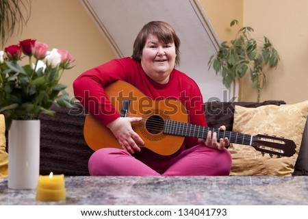 Mentally disabled woman playing guitar on a couch - stock photo