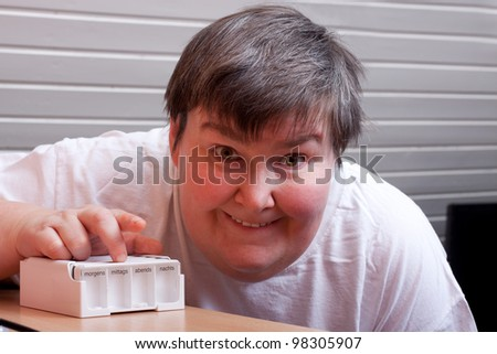 mentally disabled woman with some pills points to viewer - stock photo