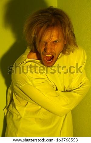 Mentally ill man in strait-jacket in room corner - stock photo