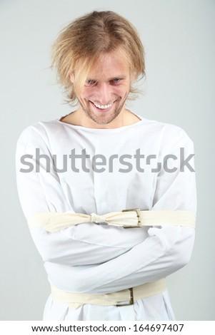 Mentally ill man in strait-jacket on gray background - stock photo