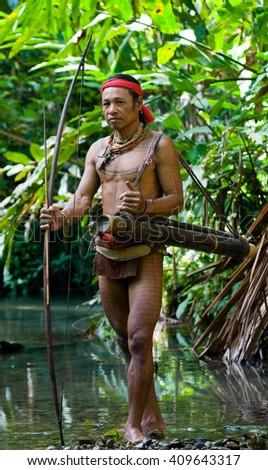 MENTAWAI PEOPLE, WEST SUMATRA, SIBERUT ISLAND, INDONESIA  16 NOVEMBER 2010: Man hunter Mentawai tribe with a bow and arrow in the jungle. 16 November, 2010. West Sumatra, Siberut island, Indonesia. - stock photo