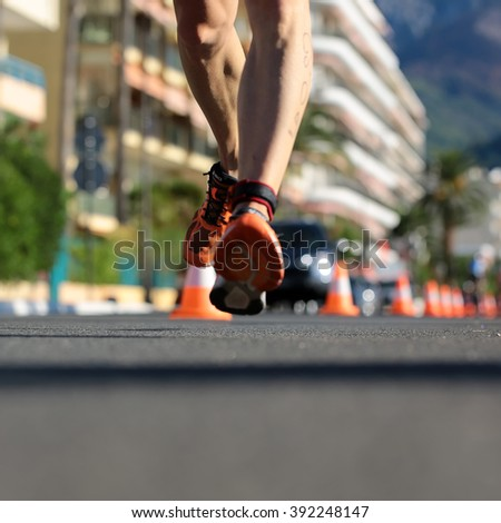 Menton, Roquebrune Cap Martin, France - September 20, 2015: legs of male runner  compete in duathlon running cross city on paved roads on streetscape background, square picture  - stock photo