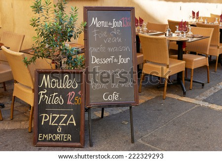 Menu and tables of street restaurant in Aix en Provence town, PACA, France - stock photo