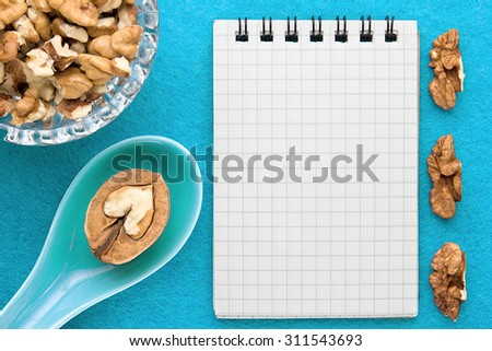 Menu background. Cook book. Recipe notebook with walnuts on a blue background - stock photo