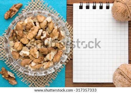 Menu background. Cook book. Recipe notebook with walnuts on a blue background and a wooden board. - stock photo