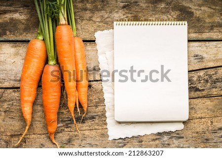 Menu background. Vegetables on table with cook book. Cooking with recipe book. Carrot - stock photo