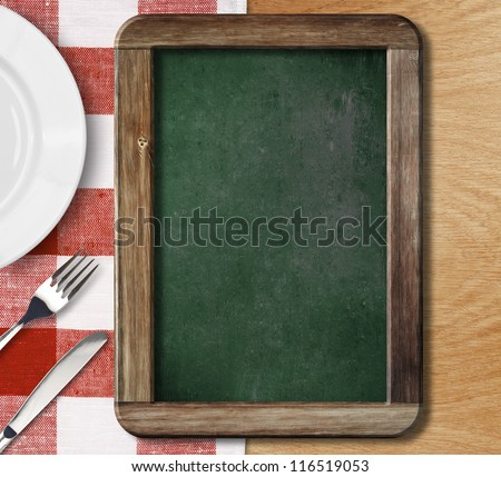 Menu blackboard lying on table with plate, knife and fork - stock photo