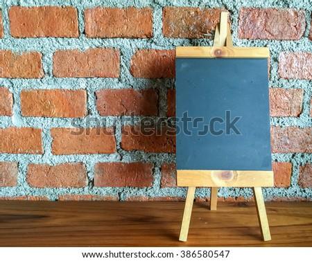 Menu blackboard on wooden table with  brick wall - stock photo