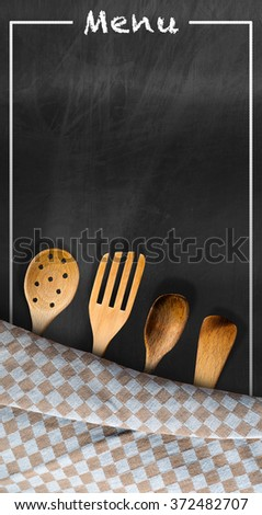 Menu - Blackboard with Kitchen Utensils / Empty blackboard with brown and white checkered tablecloth, text Menu and four wooden kitchen utensils. Template for a food menu - stock photo
