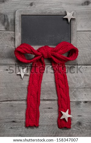 Menu board for christmas with red ribbon and stars on grey wooden background - stock photo