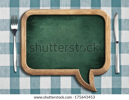 menu chalkboard on table in shape of speech bubble - stock photo